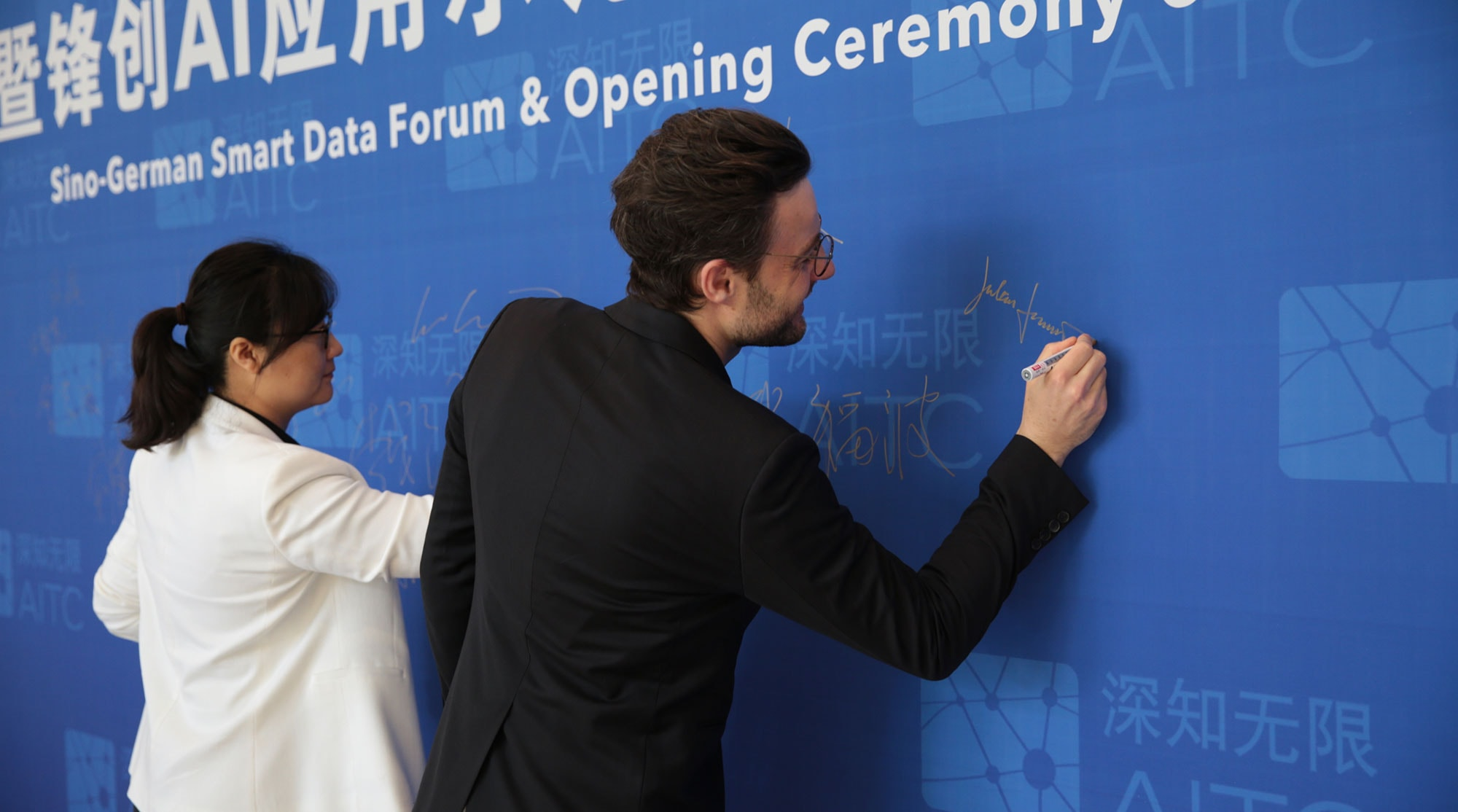 Yuan Huijin and Julian Masuhr sign wall of AI research event