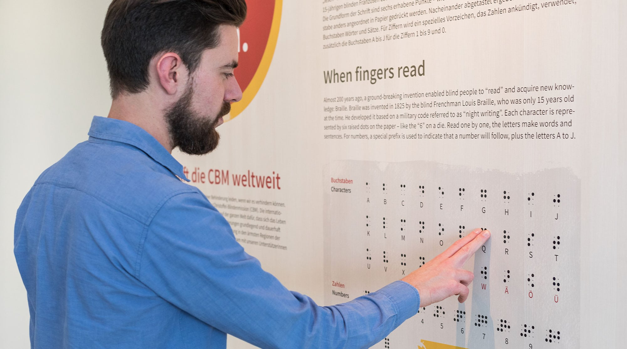 Visitor palpates braille script to understand work of CBM
